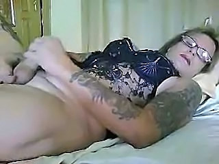 Tattooed mature shemale strokes her clit