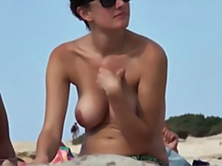 Two chicks turned on spy cam sunbathing topless at one's fingertips the beach